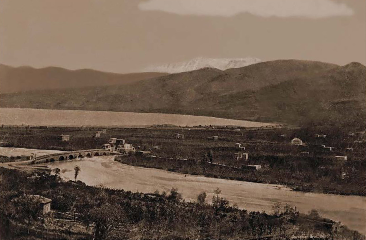 A historical photo from 1910 showing the coastal suburb of Bourj Hammoud, with agricultural lands seen on either bank of a river with a bridge crossing