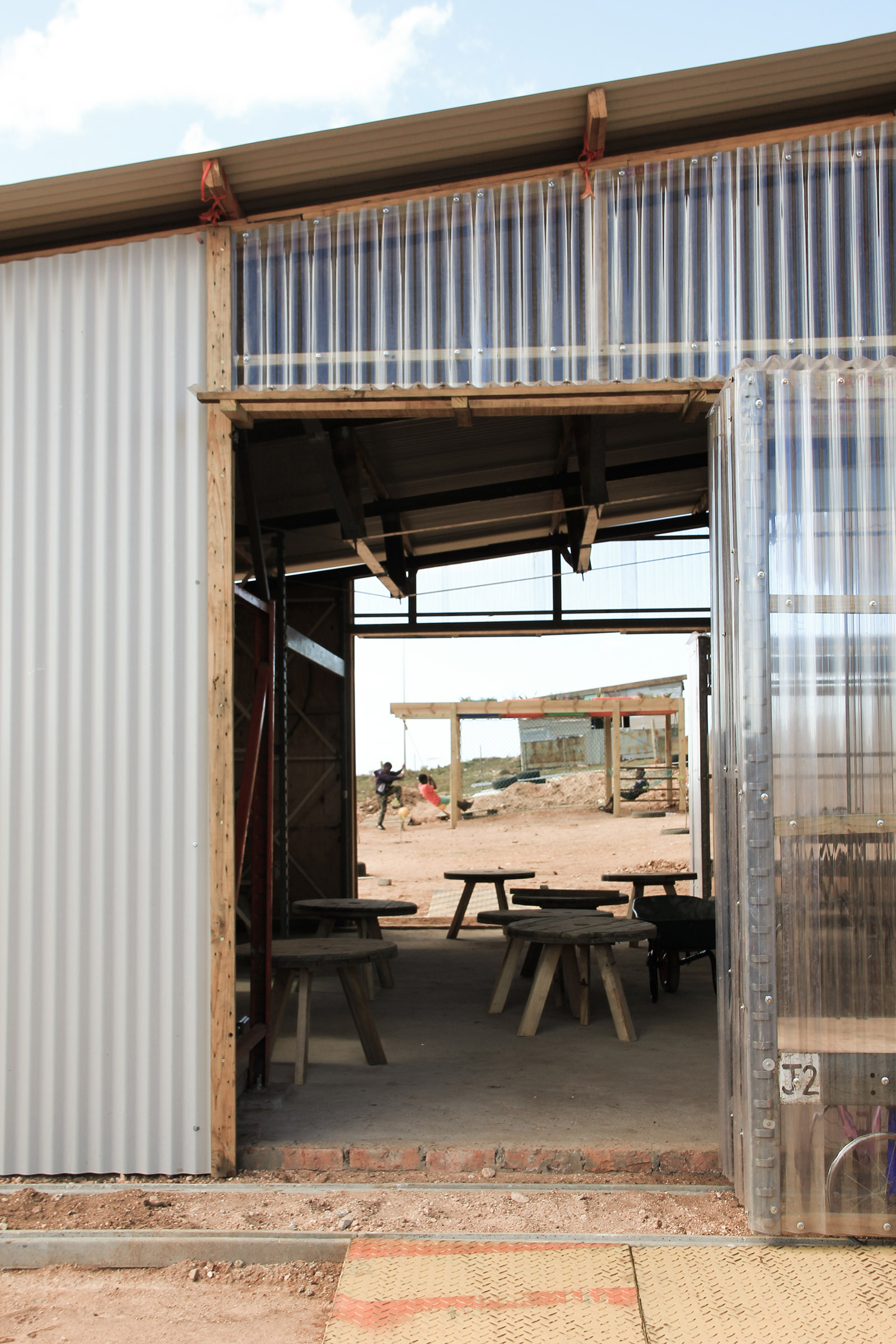 The entrance to the preschool has corrugated cladding, both opaque and transparent, set over a timber frame