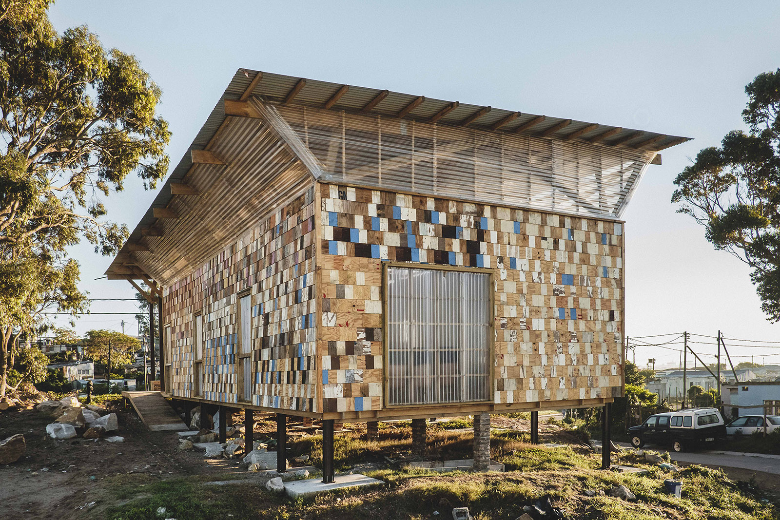 A raised structure is clad with reused, lapped timber tiles, with many painted in different colours