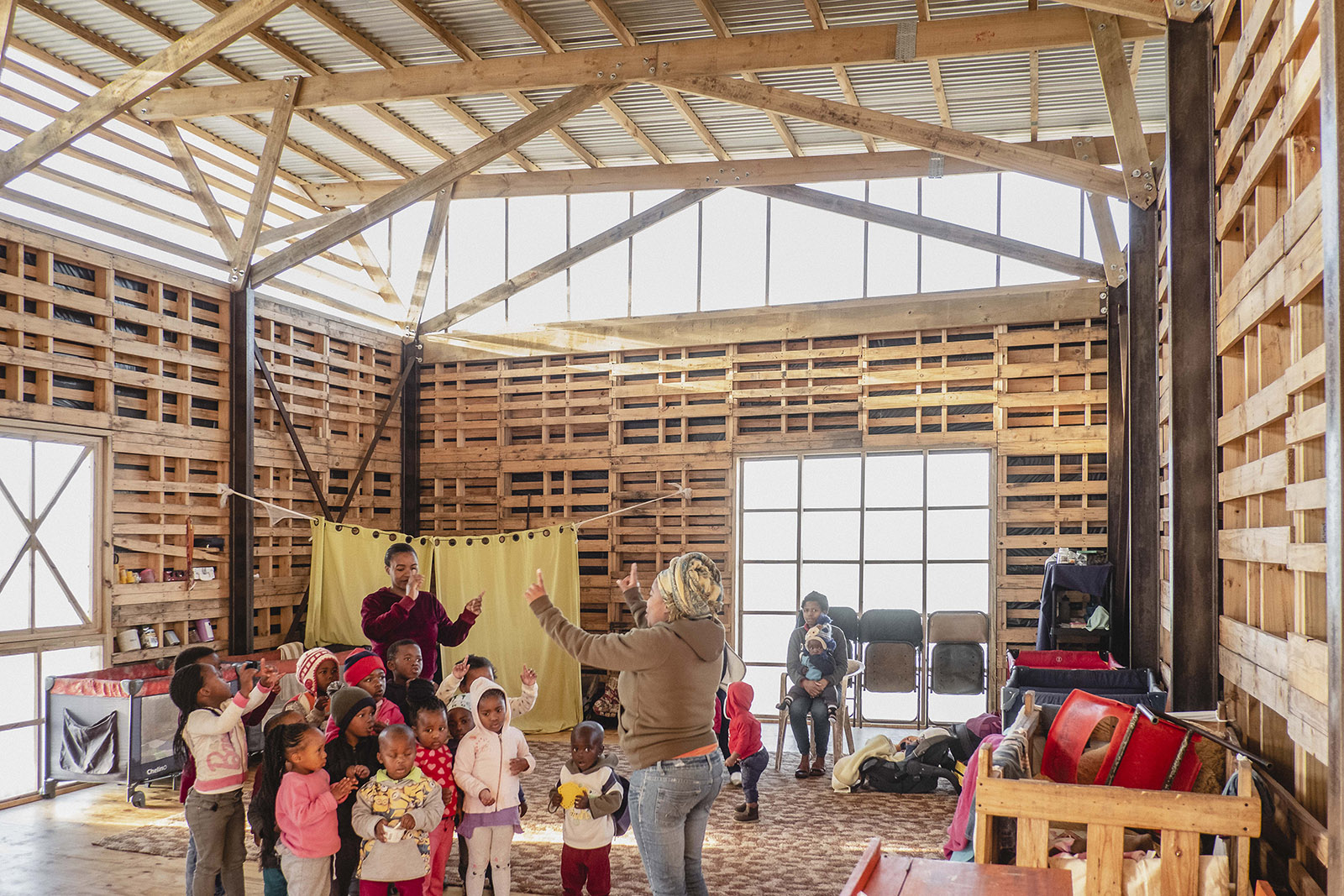 The crèche seen from the inside shows that timber pallets have been used to make the walls, with a corrugated plastic strip below the roof to introduce daylight