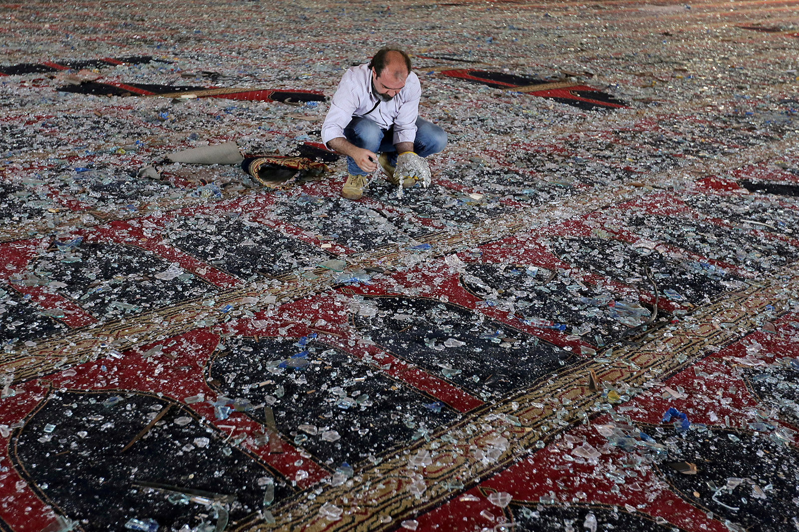 A man removes broken glass scattered on the carpet of a mosque damaged in the blast in Beirut, Lebanon in August 2020