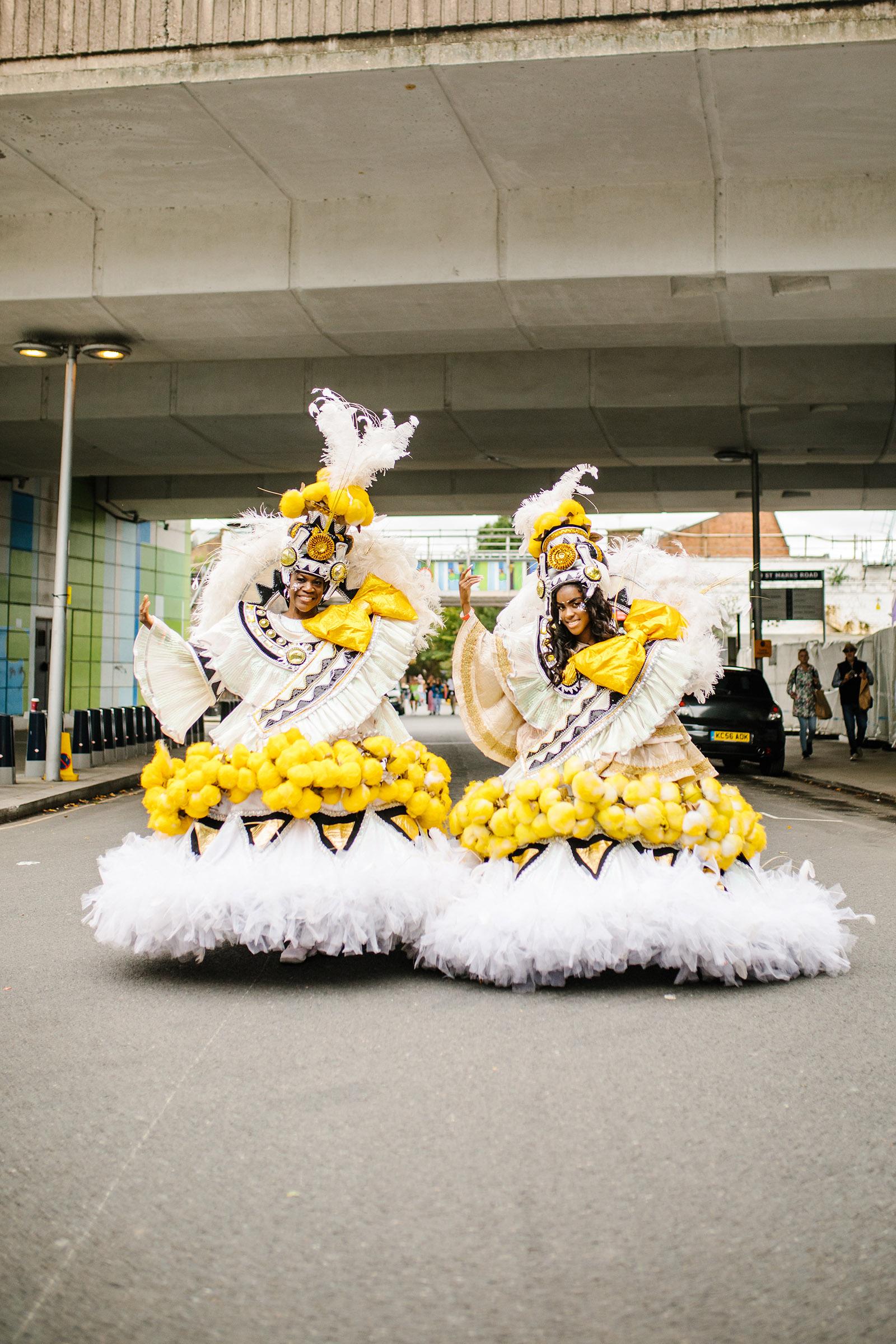 Dua orang dalam pakaian karnaval mewah berwarna kuning dan putih berdiri di tengah Ladbroke Grove di Notting Hill, dengan jembatan beton Westway terlihat di belakang mereka